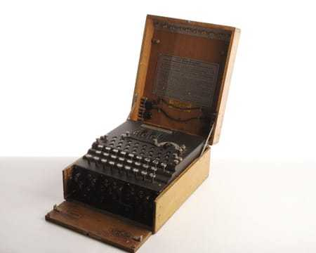 The ENIGMA machine, a typewriter-like object in a wooden box, shown open and angled to the side.