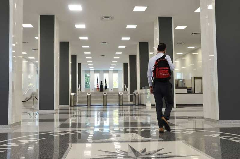CIA Officer walking down the headquarters hallway with a black and red backpack.