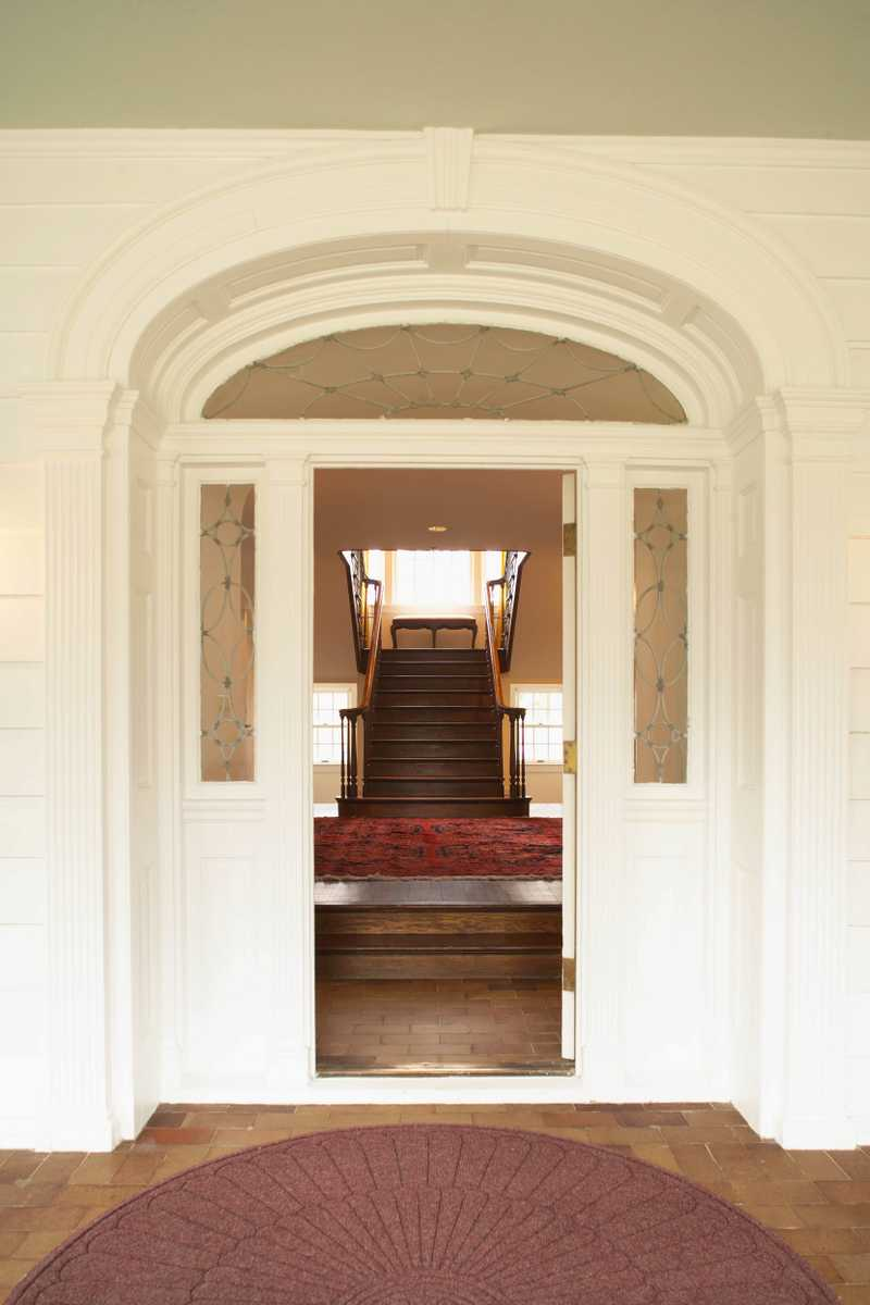 A crisp, white front entrance of the manor with the door opened and a view of the large, wooden staircase.