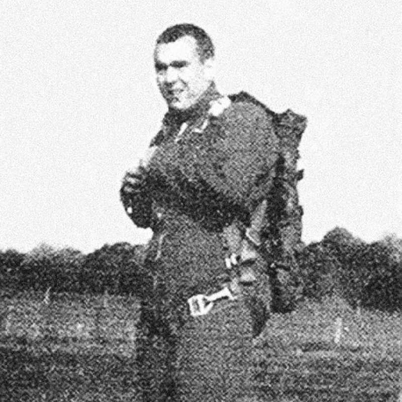 A faded black and white photograph of Michael A. Maloney standing in a field.