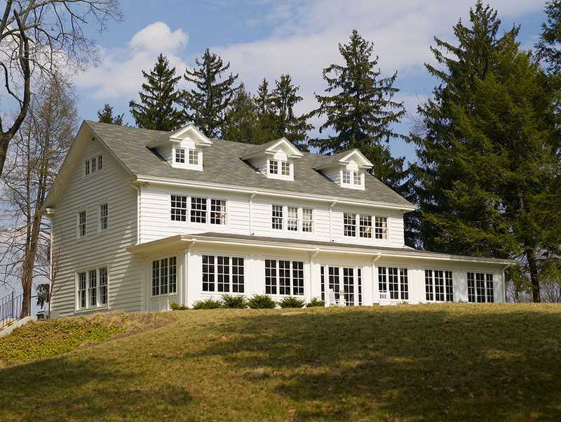 A white, colonial home with a gray roofing, surrounded by trees on the Scattergood-Thorne property.