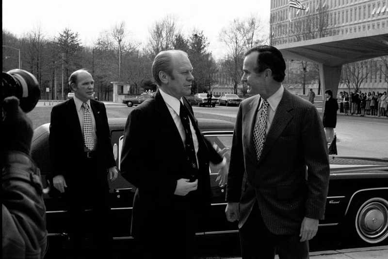 A black and white candid image of Bush and two men outside of the CIA Headquarters building standing in front of a car.