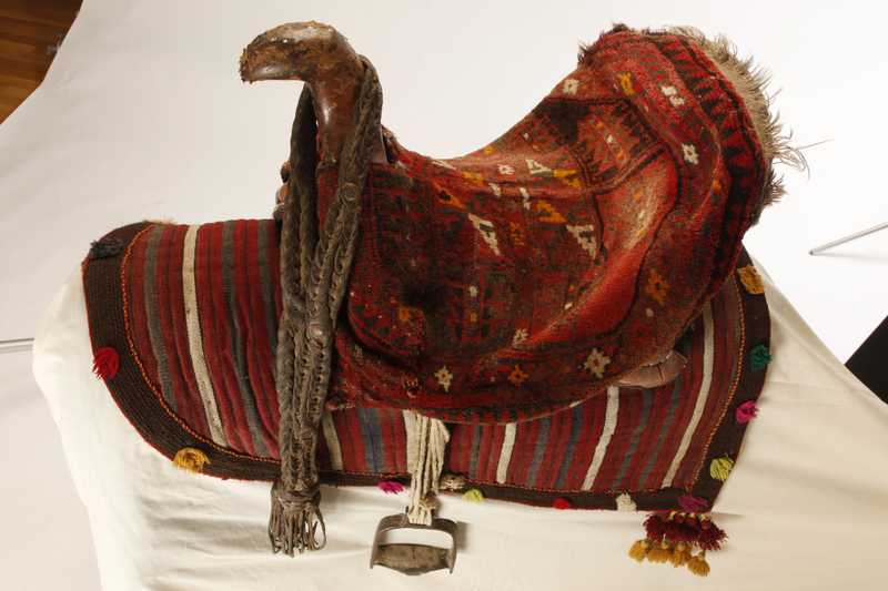 A saddle decorated with red woven cloth and tassels
