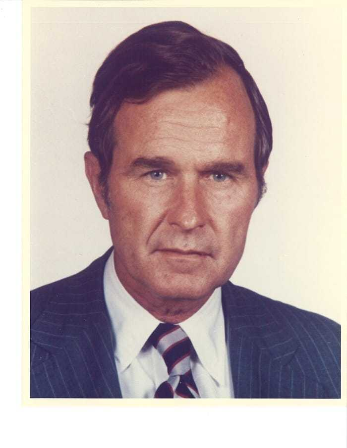 A headshot of George H. W. Bush in a blue suit with a blue and grey striped tie.