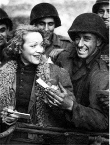 A black and white image of Marlene and four soldiers close together, smiling and looking at eachother.