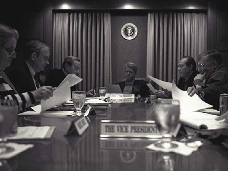 Black and white photo of a group in the boardroom each holding papers.