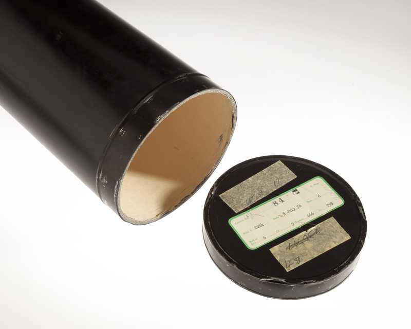 A black film canister with details about the film written on the lid