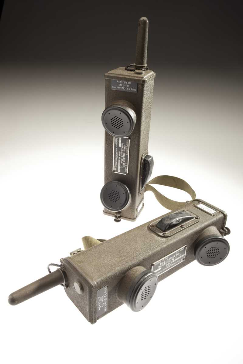 Two rectangular walkie-talkies, each with a mouthpiece and earpiece.