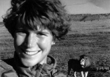 A black and white selfie of Leslianne Shedd with a lion in back.