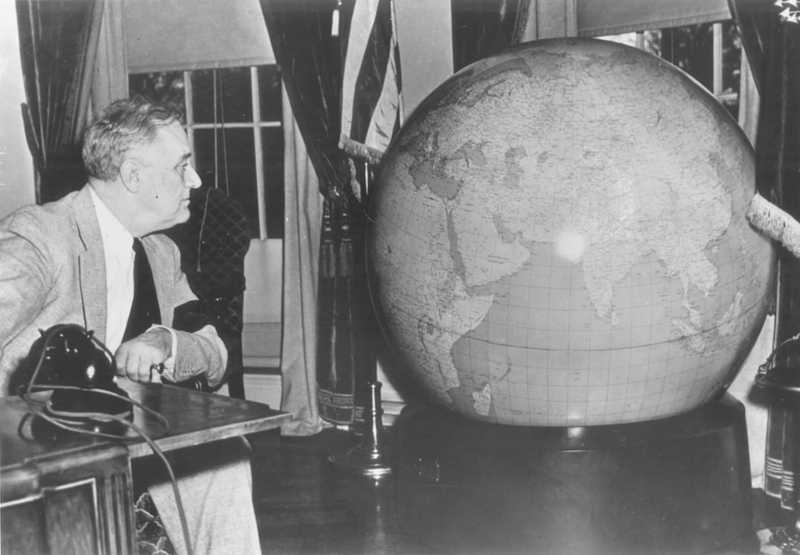 President Roosevelt looking at a large globe.