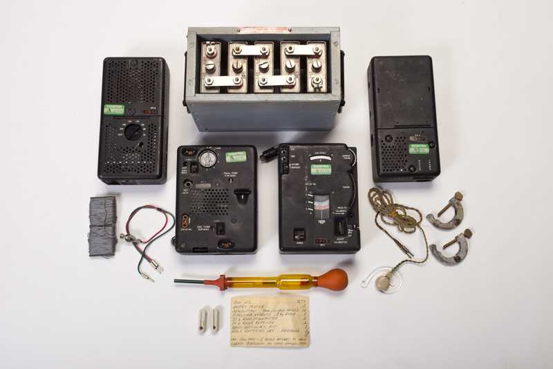 A set of four radios and speakers, surrounded by wires and other instruments to power the radio.