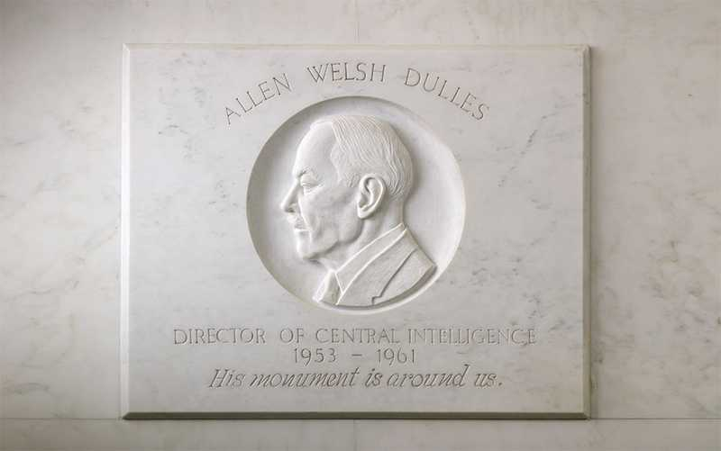 A white, marble bas-relief of a former CIA officer marked by his name, title, birth year and death year.
