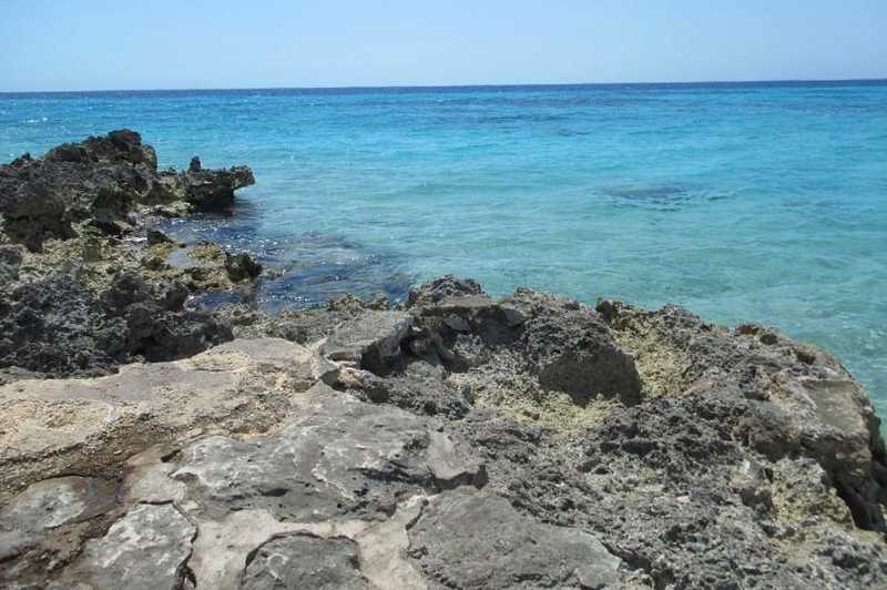 A rocky shore against a turquoise sea at Bay of Pigs, Cuba.