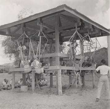 Soldiers sitting in parachute harnesses suspended from wooden beams.