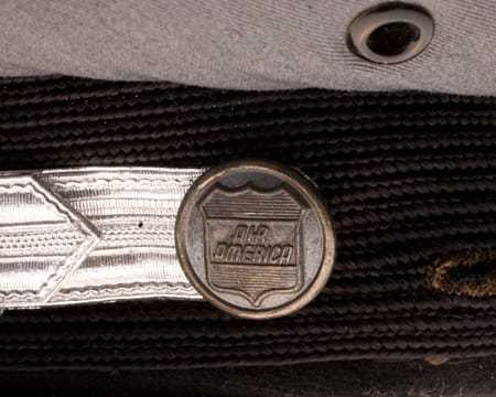 A metal button on the side of the cap, also displaying the Air America logo