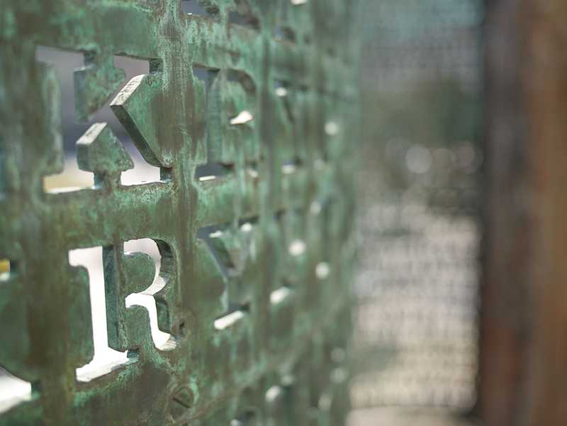 An up-close shot of the letters K and R inscribed in the copper screen with a blurred background.
