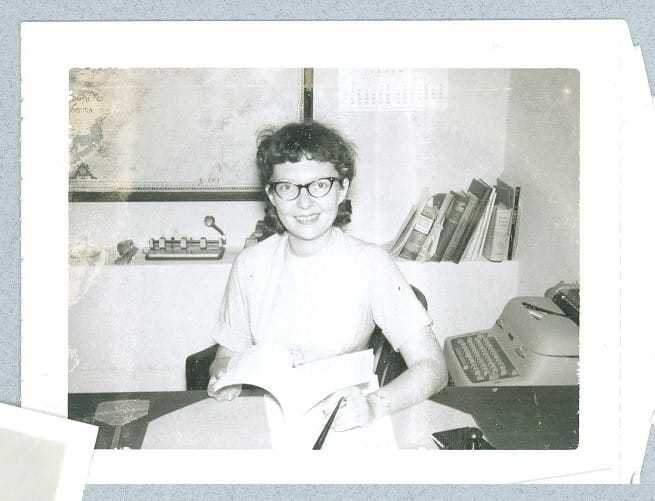 Jeanne Vertefeuille sitting at a desk holding a book open.