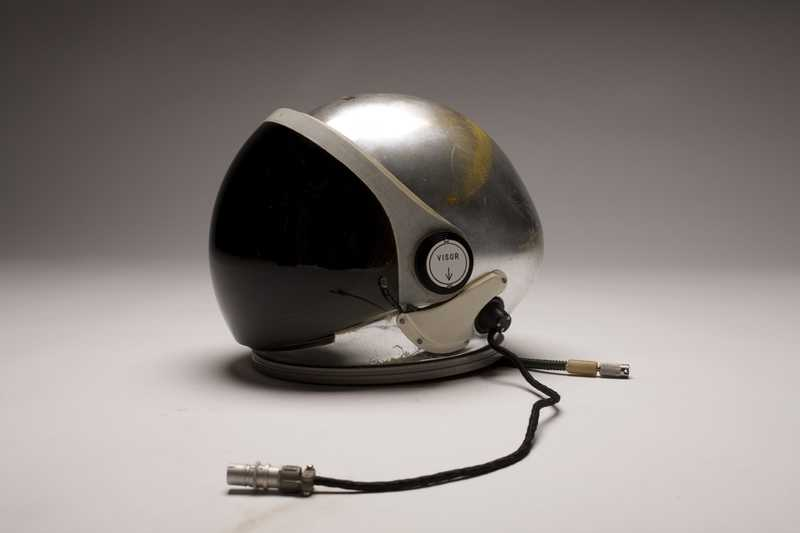 A silver A-12 pilot's helmet with a large visor and cords to connect to the suit
