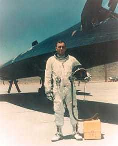 An A-12 Oxcart pilot in a pilot's suit standing in front of the plane.