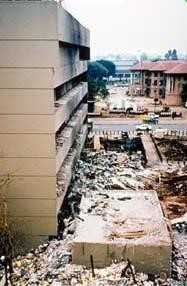 The aftermath of a bomb with debris where a building once stood and black ash covering the building next to the debris.