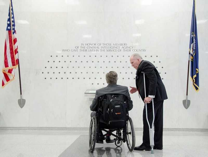 Bush, in a wheelchair, and Director John Brennan, with a crutch under his left armpit, looking at a memorial inscribed on the sheen white wall inside the entrance of the CIA Headquarters Building.