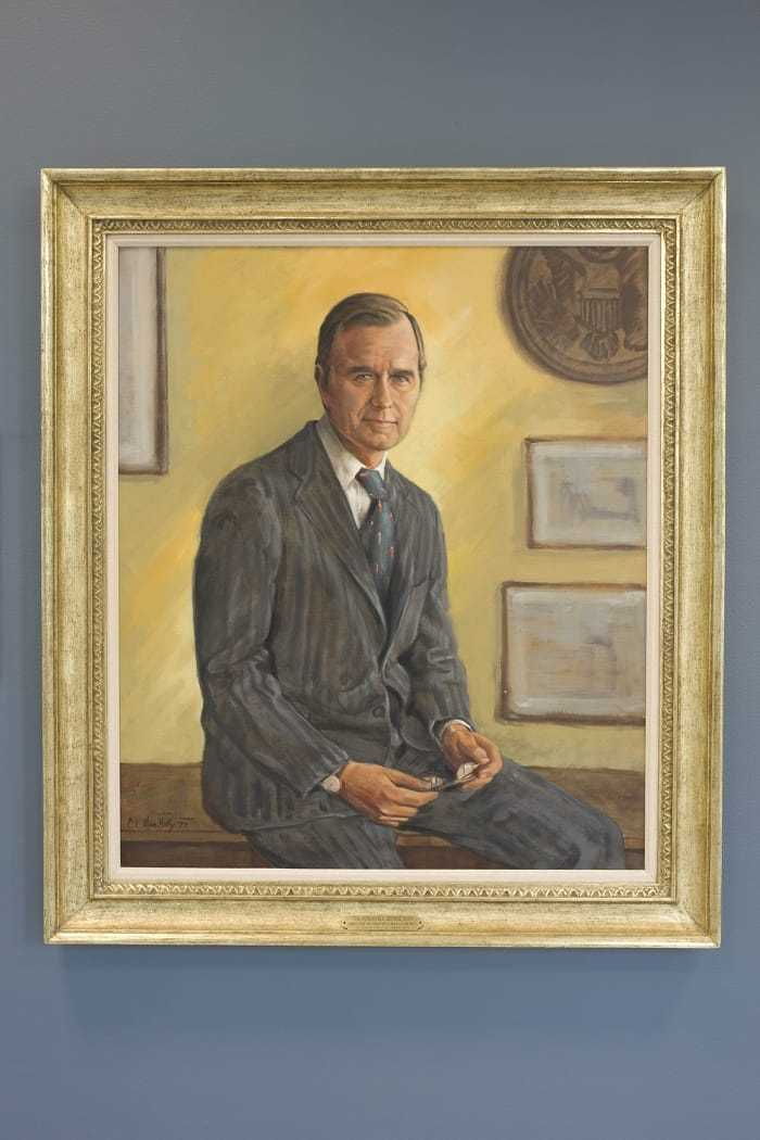 A painting of Bush sitting on a desk, with his hands laying on his lap, in a gold frame hanging on a blue wall.