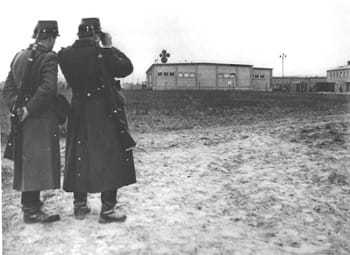 Two East German police looking at a warehouse building on the compound.
