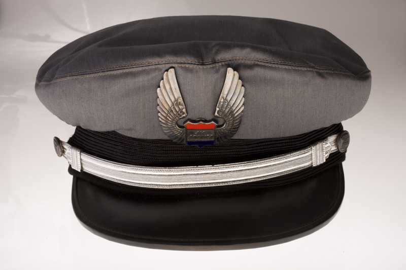 A pilot's cap with a metal Air America logo pinned to the front