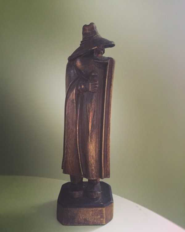 A small wooden carving of a figure in long cloak and large hat drooping down to cover its face.