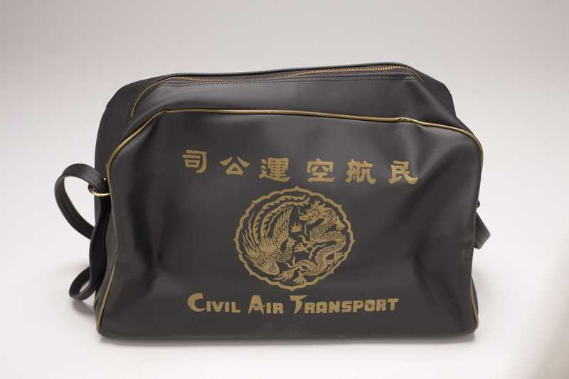 A black zippered bag with the CAT logo printed in gold on the side