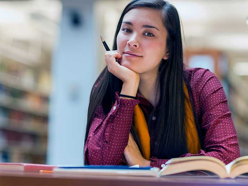 A young woman in a library holding a pen in front of a desk with several open books.