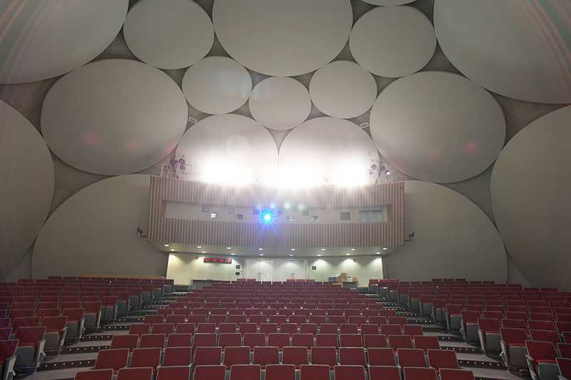 A rear stage-view of the theater inside the CIA Headquarters Auditorium, with stage lights turned on.