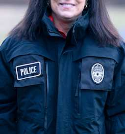 A woman in a dark colored police jacket.