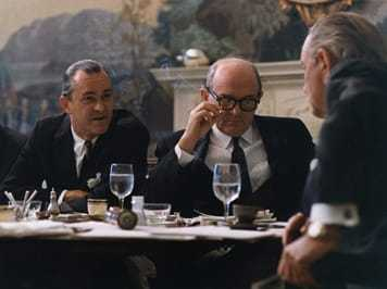 An image of Richard M. Helms sitting a table with two other men.