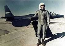 image of a man standing in front of an airplane.