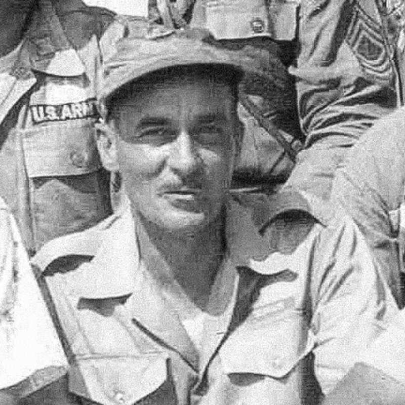 A black and white close up of Jennings Benson smirking at the camera in his army uniform surrounded by other soldiers in uniform.