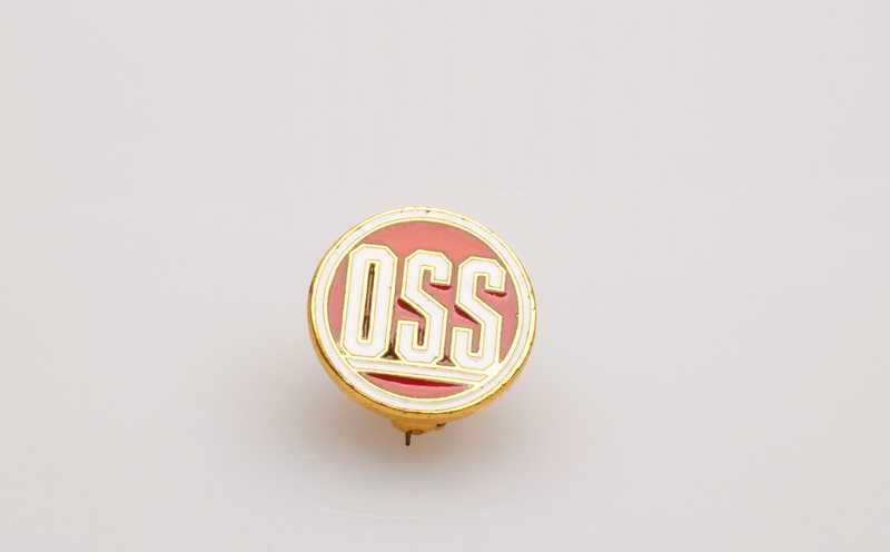 A red, gold, and white OSS pin.