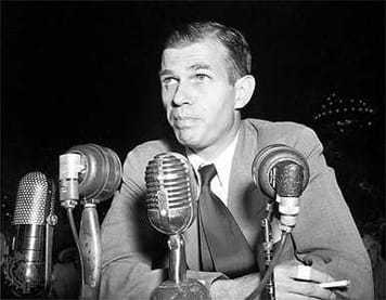 Image of Alger Hiss with microphones in front of him.